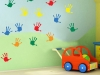 nursery children hand prints in colour on a wall with a toy in front of the wall