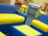 furniture inside a nursery of yellow and blue sofa, tables and stools